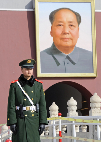 An unidentified soldier stands guard in front of a portrait of Mao. (Credit: Hung Chung Chih - Shutterstock.com)