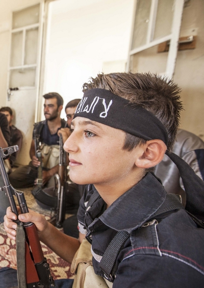 A young boy with rebel soldiers in Syria.<br /> (Credit: Dona_Bozzi - Shutterstock.com)