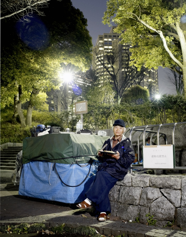 tokyo - shinjuku central park - shinjuku gyoen - homeless people living in boxes and tents in the park - man having dinner next to his hut -